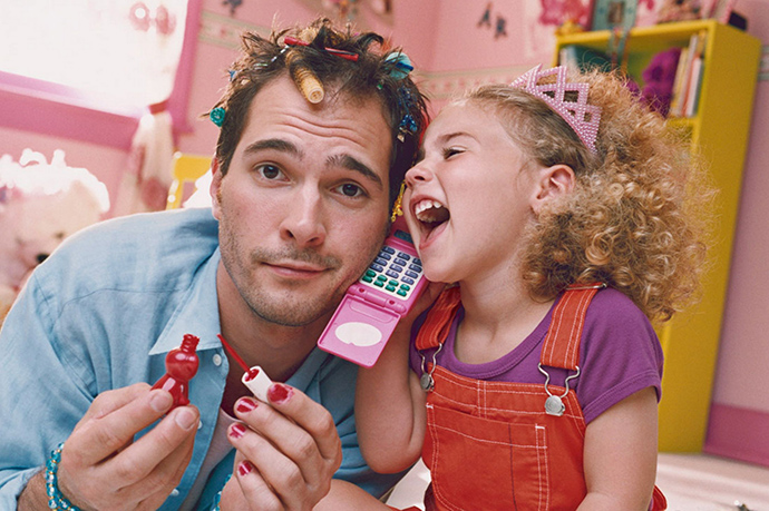 Daughter playing with father with hair curlers and nail polish