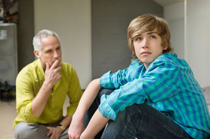 Man-sitting-with-his-son-looking-upset