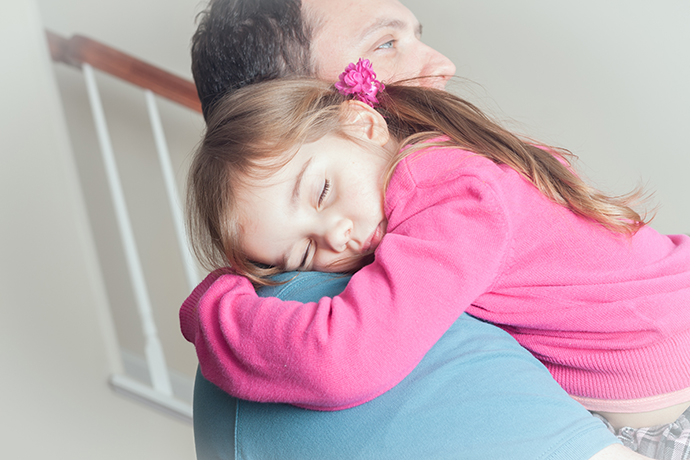 litle girl sleeping in dad's arms