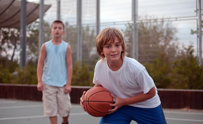 Teenagers play basketball .