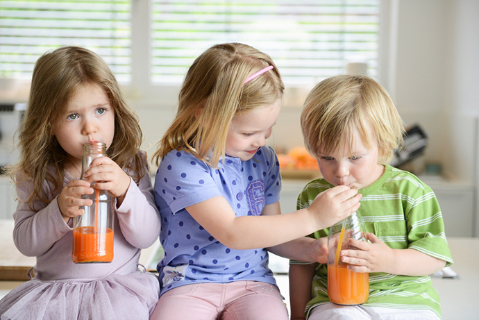 Girl helping brother drink orange juice in kitchen