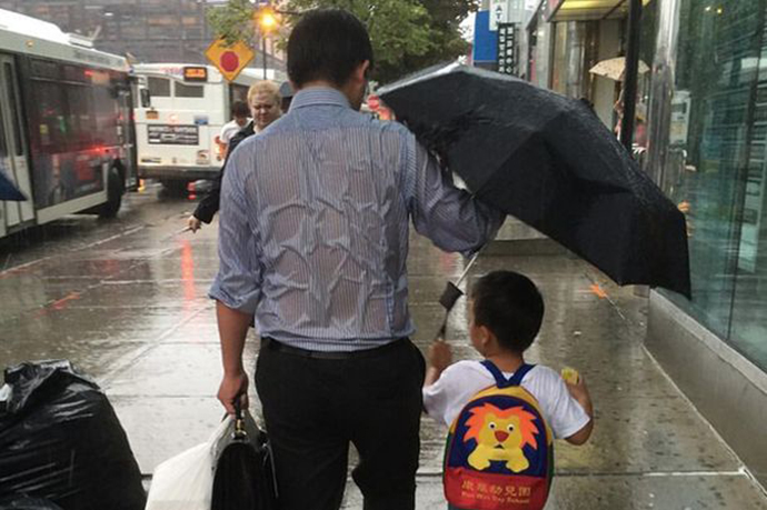 Dad-putting-him-kid-first-holding-umbrella-over-him