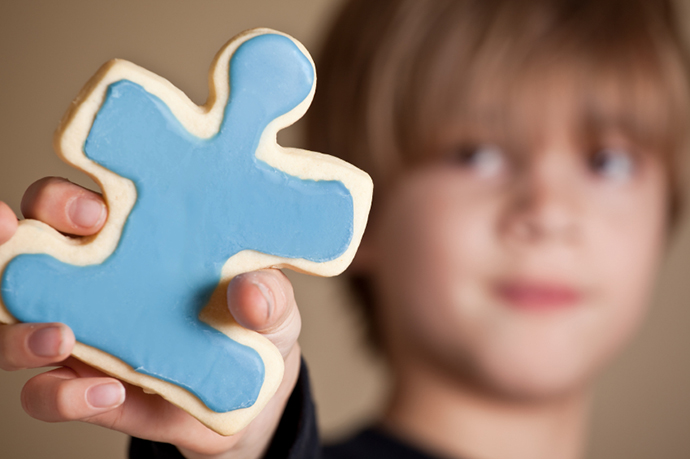 Boy Holding Blue Iced Puzzle Piece Cookie