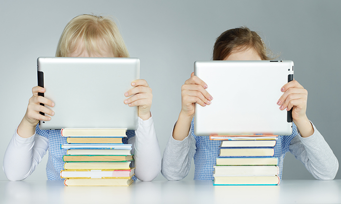 Two pupils leaning on a pile of books while reading on touchpad